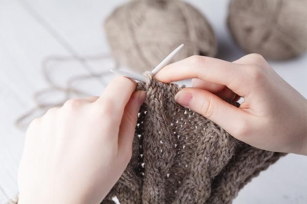 Женщина вяжет шерстяную одежду. вязальные спицы. крупный план. натуральная шерсть