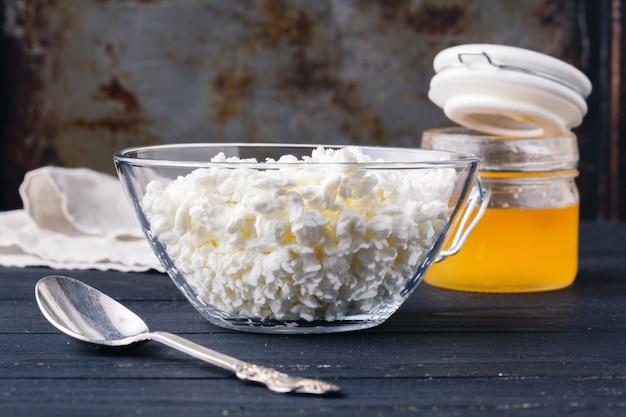 素朴なテーブルの皿で自家製の天然脂肪カッテージチーズ