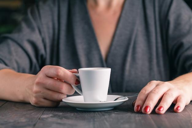 手と一杯のコーヒーの写真をクローズアップ