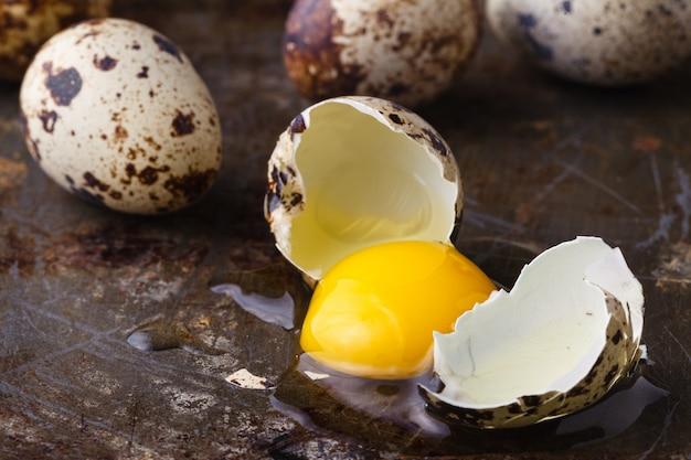 Перепелиное яйцо сломано на деревенском столе