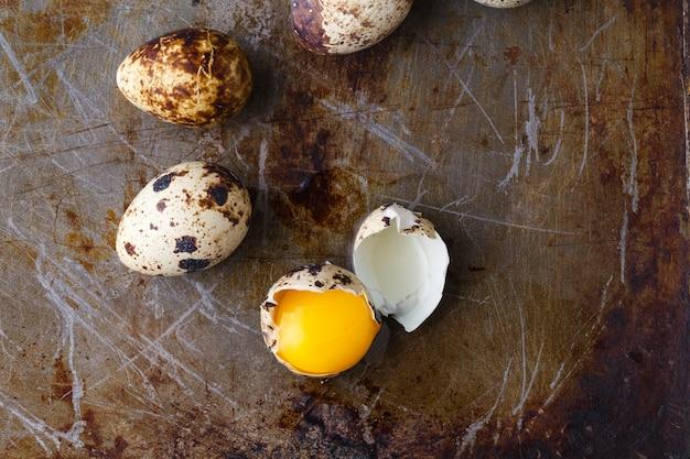 Перепелиное яйцо сломано на деревенском фоне