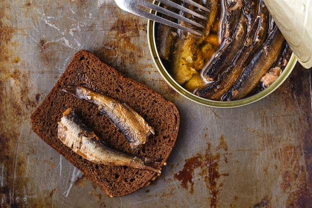 Жареная сардина на темной поверхности с хлебом