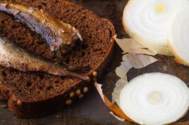 Консервированные шпроты в консервной банке с ржаным хлебом. на деревенской поверхности