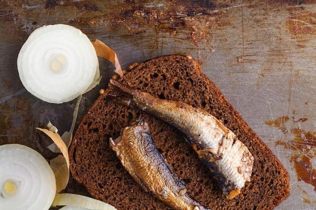 Открытые рыбные консервы, вилка и хлеб
