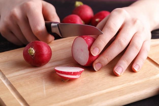 Вырезать красный свежий редис на деревянной доске