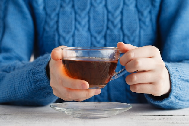 Женщина держит чашку чая в руках