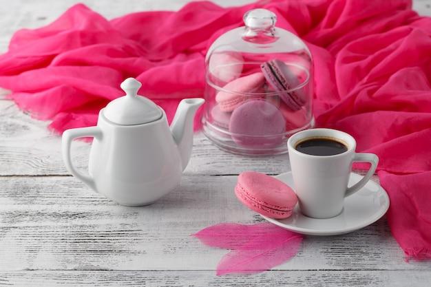 Женский завтрак с кофейной чашкой и розовым миндальным печеньем