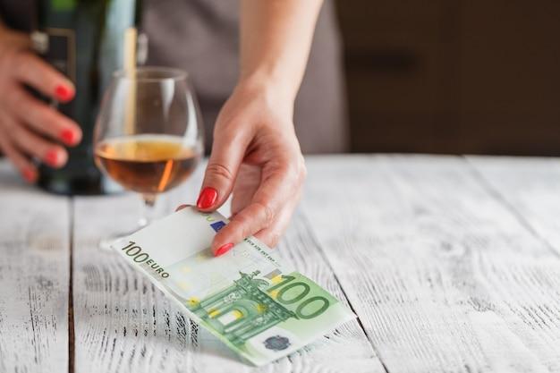 Женщина готова платить виски с банкнотами евро