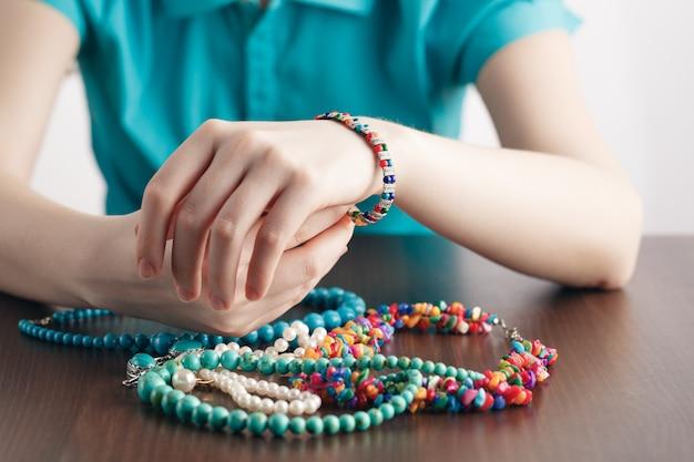 Девушка кладет на руку браслет и кучу украшений