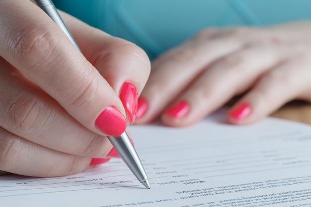 Женщина подписывает контракт