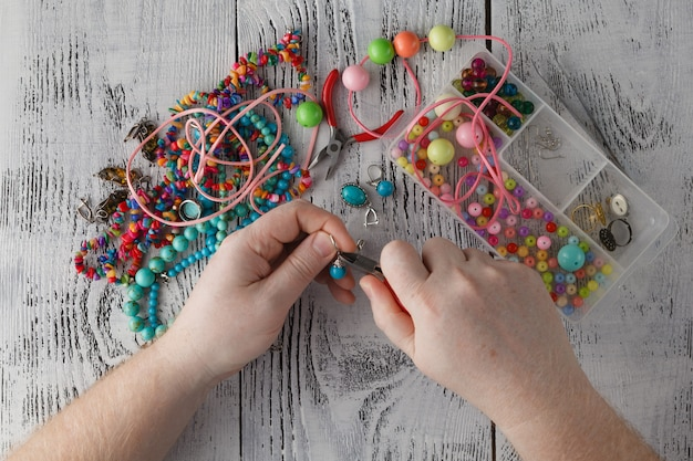 ポリマークレイのイヤリングを作る男の手。