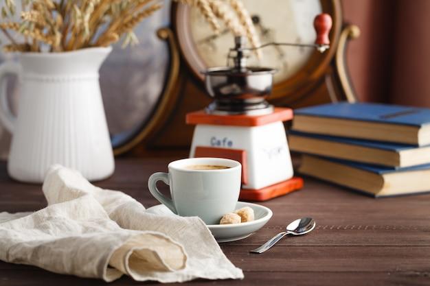 Чашка кофе с блюдцем с мешком с кофейными зернами на черном