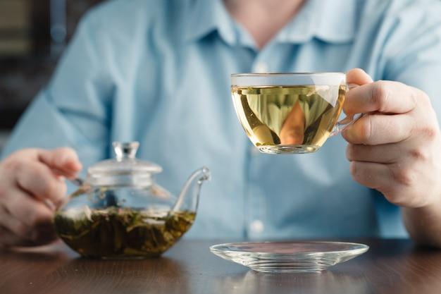 Человек предлагает чайную чашку