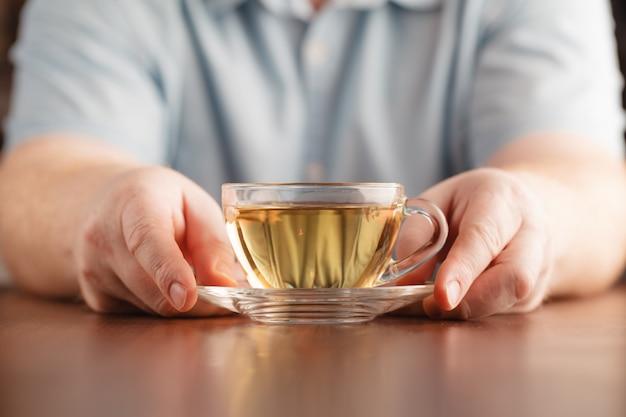 Мужчина держит чашку в руке и предлагает чай