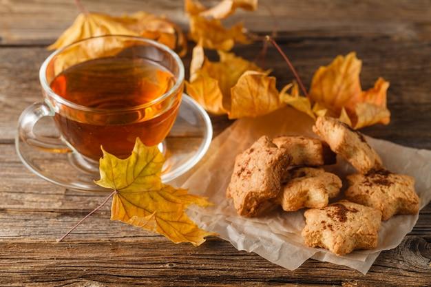 Чашка горячего чая на деревянный стол с листьями. осень.