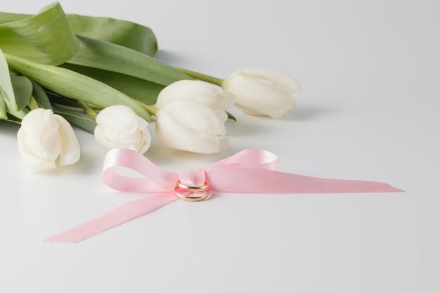 Красивые белые тюльпаны, розовая лента и обручальные кольца