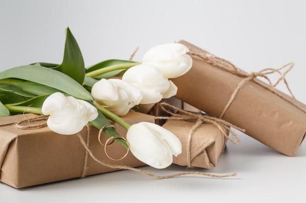 Подарочная коробка и букет тюльпанов на белой поверхности