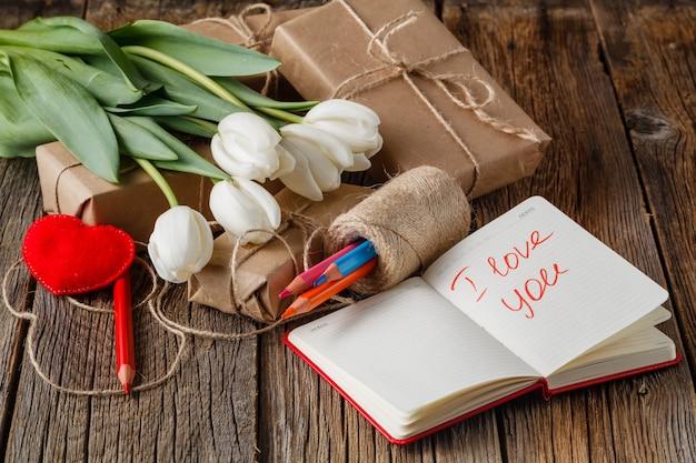 Я люблю тебя фразу в блокноте с цветами на столе