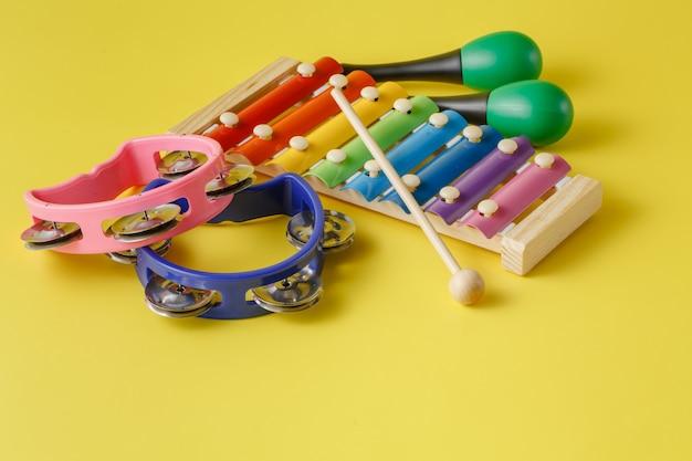 Коллекция музыкальных инструментов на желтой поверхности