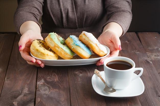 Женщина держать тарелку с пончиками.