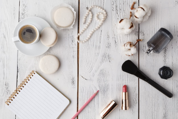 Губная помада, кисточка для макияжа и пустой бумажный фон для заметок