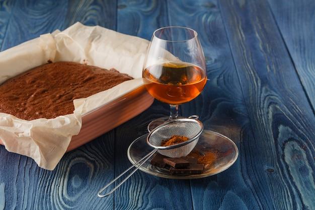 Домашнее шоколадное пирожное в сковороде из духовки на темном деревянном фоне