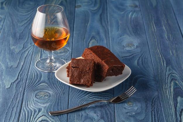 セレクティブフォーカスのバックグラウンドでチョコレートのブラウニーと木製のトレイにラム酒のガラス