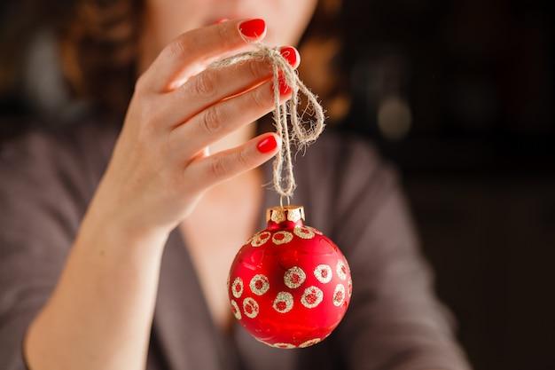 指でクリスマスボールを保持している女の子。赤いボールの背景に美しいマニキュア。