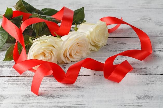 バラと木の板、バレンタインデーの背景、結婚式の日のリボン