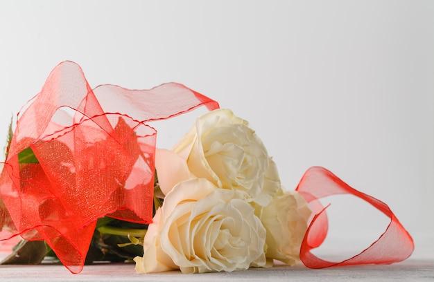 Крупным планом розы и красная лента на белом