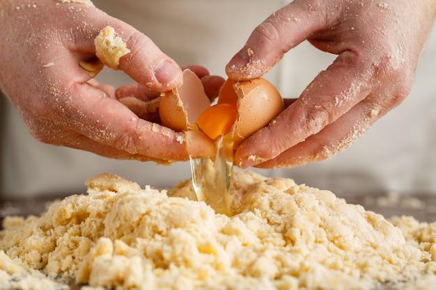 男性シェフが準備します。男は泡立て器の卵を混ぜます。上面図