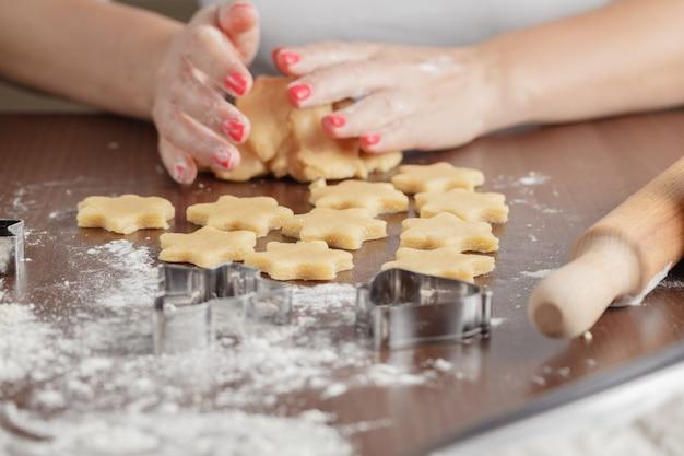 料理と家のコンセプト-自宅で新鮮な生地からクッキーを作る女性の手のクローズアップ