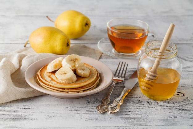 蜂蜜とパンケーキのスタックと素朴な木製の背景にバナナのスライス