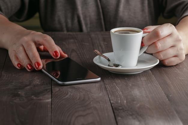 Женщина пьет кофе в кафе и смотрит на экран телефона