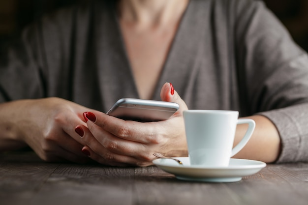 電話と一杯のコーヒーを保持している女性の手