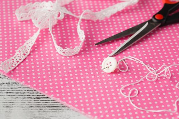 Игла и кнопка на розовой ткани в горошек