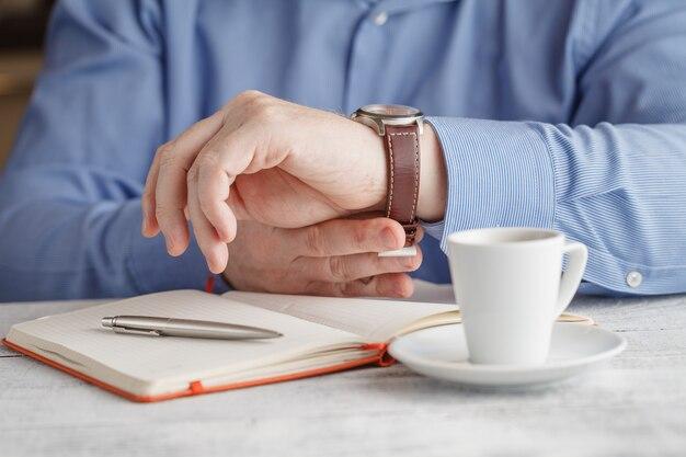 Изображение крупного плана человека выпивая вкусный кофе эспрессо на переднем плане