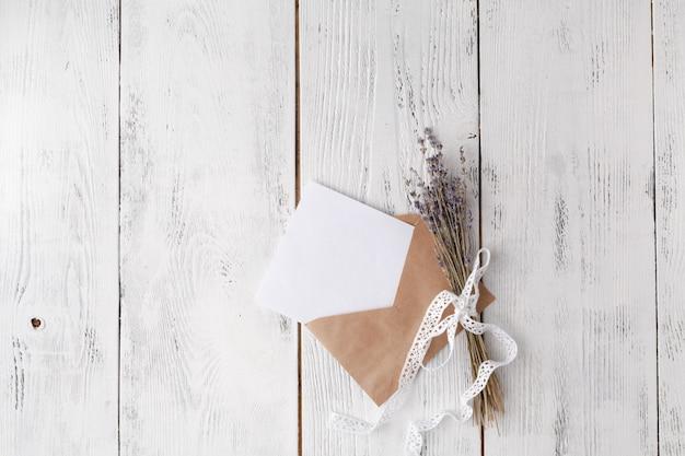 木製のテーブル上の封筒と結婚式の招待カード
