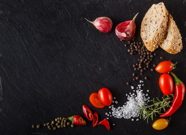 スライスしたパンと塩とスレートの赤いチェリートマト。