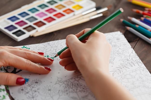 Взрослая женщина снимает стресс, рисуя книжку-раскраску для отдыха
