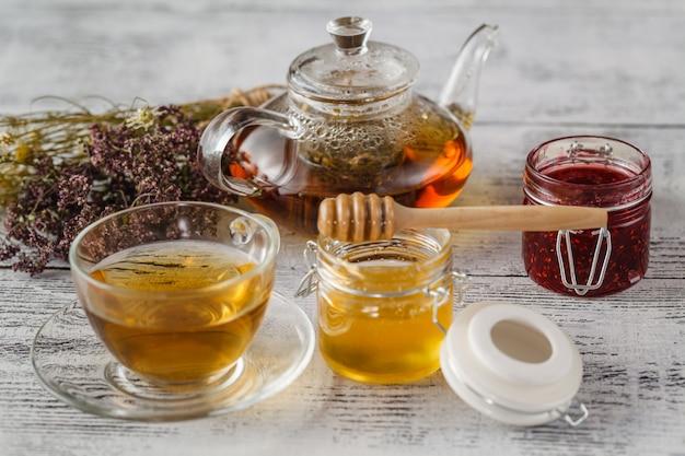 Чашка травяного чая с полевыми цветами и различными травами