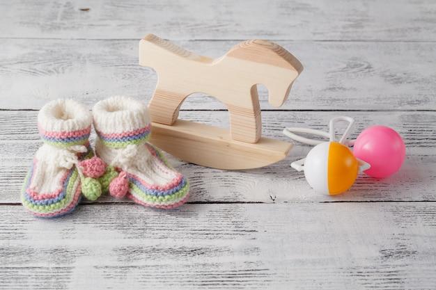 誕生日の招待状。新生児のためのガラガラ、木製の馬とニットのブーツ