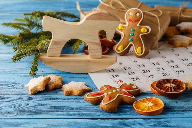 クリスマスのモミの木、ギフトボックス、休日のクッキー、カレンダー付きのテーブルの装飾