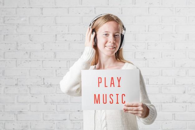 喜びで音楽を聴くヘッドフォンを持つ女性