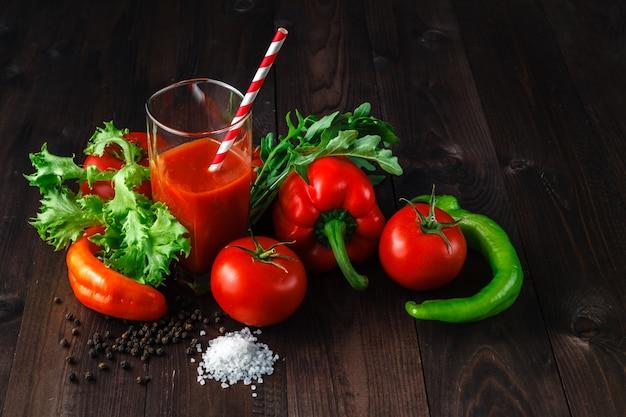 素朴な木製のテーブルにハーブとフレッシュトマトジュース