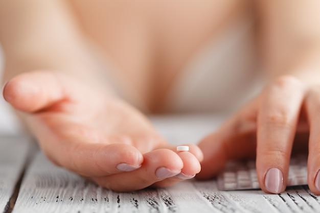 Женщина, держащая противозачаточные средства