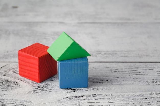 木製の背景に自然な色のおもちゃブロックの家