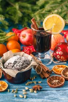 スパイシーで甘いアレンジメントのホットワインドリンク、古い木製のテーブルで撮影