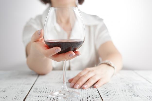 赤ワインの女性に触れるガラス