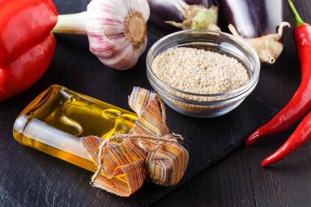 Кунжутное масло и семена на китайском японском столе с палочками